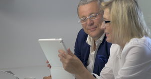 Businesspeople Working with Tablet. Mature businesspeople are watching something in tablet, discussing it and laughing stock video footage