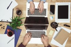 Businesspeople working and typing on laptops at workplace with gadgets and office supplies. Top view of businesspeople working and typing on laptops at workplace royalty free stock photo