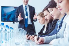 Businesspeople writing during conference stock photo
