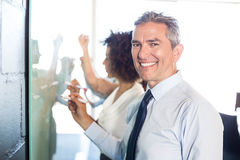 Businesspeople writing on white board. In office Stock Photography