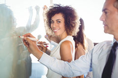 Businesspeople writing on white board Royalty Free Stock Images