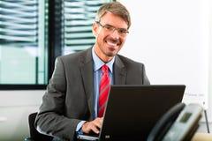 Businessperson με το lap-top στο επιχειρησιακό γραφείο του Στοκ εικόνα με δικαίωμα ελεύθερης χρήσης