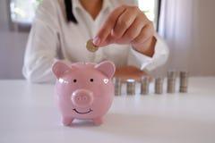 Businessperson που παρεμβάλλει τα νομίσματα στην τράπεζα Piggy με το σωρό των νομισμάτων πέρα από το γραφείο στοκ εικόνες
