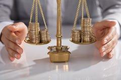 Businessperson που προστατεύει την κλίμακα δικαιοσύνης με συσσωρευμένος των νομισμάτων στοκ φωτογραφίες