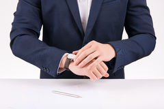 Businessperson adjusting his wristwatch. Busy person. Business worker is adjusting his wristwatch while standing at the desk Royalty Free Stock Image