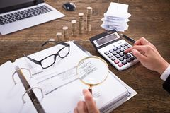Businessperson Analyzing Bill With Magnifying Glass royalty-vrije stock afbeelding