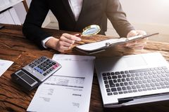 Businessperson Analyzing Bill With Magnifying Glass stock fotografie
