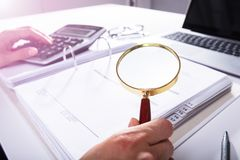 Businessperson Analyzing Bill With Magnifying Glass stock foto's