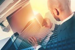 Businessperson in bureau dat op Internet-netwerk aan laptop wordt verbonden royalty-vrije stock afbeelding