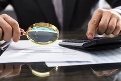 Businessperson Calculating Bill With Magnifying Glass stock afbeeldingen