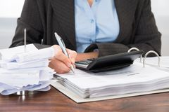 Businessperson calculating bills Stock Photo