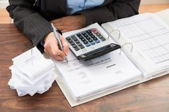 Businessperson calculating bills Stock Photography