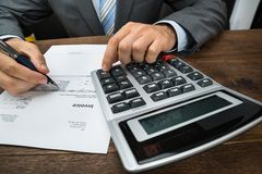 Businessperson calculating financial sheet Royalty Free Stock Image