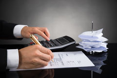 Businessperson Calculating Invoice At Desk Royalty Free Stock Photography