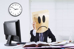 Businessperson with cardboard head sitting in office Royalty Free Stock Images