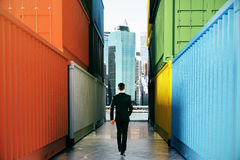 Businessperson between cargo containers. Businessperson walking towards city on concrete path between cargo containers. Success concept, 3D Rendering Royalty Free Stock Photography