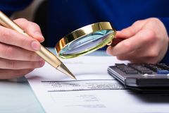 Businessperson Checking Bill Through Magnifying Glass stock foto