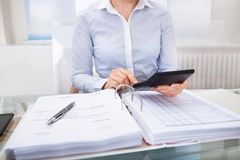 Businessperson checking an invoice in office Stock Photos