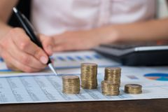 Businessperson With Coins Over Graph And Report Stock Photos