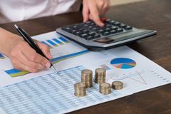 Businessperson With Coins Over Graph And Report Stock Images