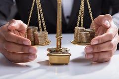 Businessperson Covering Stacked Coins på vägningsskala arkivbilder
