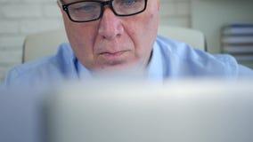 Businessperson in de Documenten van de Bureaulezing en Bedrijfsgegevens op Laptop stock video