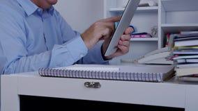Businessperson in de tekst die van de bureauruimte een tablet gebruiken verzendt en ontvangt berichten stock videobeelden