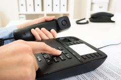 Businessperson dialing number on telephone keypad Royalty Free Stock Image