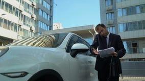 Businessperson die op telefoon dichtbij auto spreken, die bedrijfskwesties van bedrijf bespreken stock footage