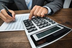 Businessperson doing calculation in office. Close-up Of Businessperson Doing Calculation With Calculator In Office Stock Photography