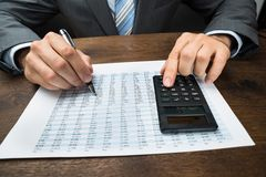 Businessperson doing calculation in office Stock Image
