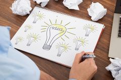 Businessperson drawing bulb on book Royalty Free Stock Images