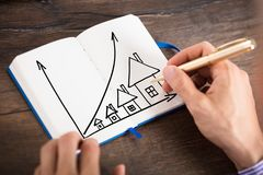 Businessperson Drawing The Houses Chart On Diary. Elevated View Of A Businessperson Drawing The Increasing House Chart On Diary With Pen Royalty Free Stock Photos