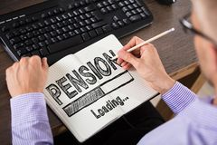 Businessperson Drawing Pension Concept på anteckningsboken royaltyfri fotografi