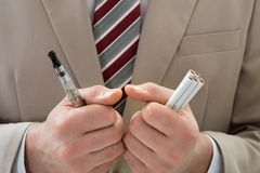 Businessperson with electronic cigarette Stock Photos