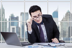 Businessperson gaze at camera in office. Middle eastern young businessman staring at the camera seriously with laptop and paperwork on desk, shot in the office Stock Images