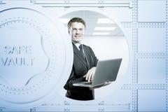Businessperson gebruikend laptop binnen bankkluis Stock Foto's