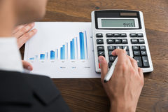 Businessperson With Graph And Calculator At Desk Stock Photography