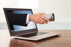 Businessperson hand with cans phone from laptop Royalty Free Stock Photo