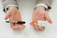 Businessperson hand with electronic cigarette Royalty Free Stock Photos