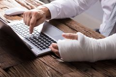 Businessperson With Hand Injury Gebruikend Laptop stock foto