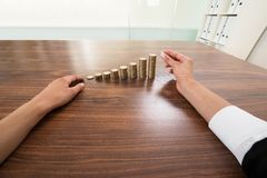 Businessperson hand putting coin to stack of coins Royalty Free Stock Photography