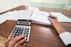 Businessperson hands calculating bill Stock Image