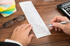 Businessperson hands with receipt and eyeglasses Royalty Free Stock Photography