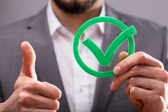Businessperson Holding Check Mark Icon arkivbilder