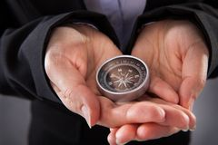 Businessperson holding compass. Close-up Of Businessperson Holding Compass In Hand stock image