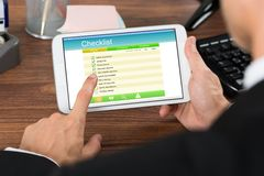 Businessperson holding mobile phone with checklist Royalty Free Stock Photos
