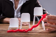 Businessperson Holding Red Arrow Showing Upward Direction. In Front Of Chairs On Wooden Desk royalty free stock photo