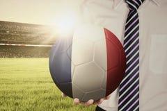 Businessperson holds ball in stadium Stock Photo