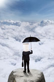 Businessperson holds umbrella on mountain Royalty Free Stock Photography